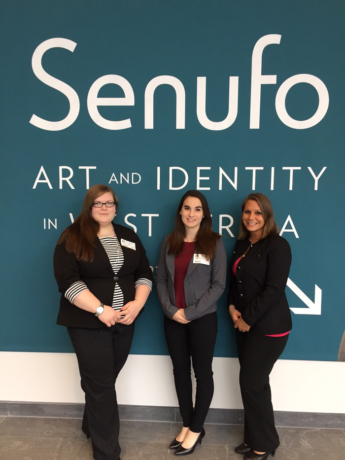 """Standing under the sign for the """"Under the Senufo: Art and Identity in West Africa"""" at the Cleveland Museum of Art are YSU students Jennifer Heitger, Emily Young and Marcy Angelo. They were the presentation team for a case study at the museum."""
