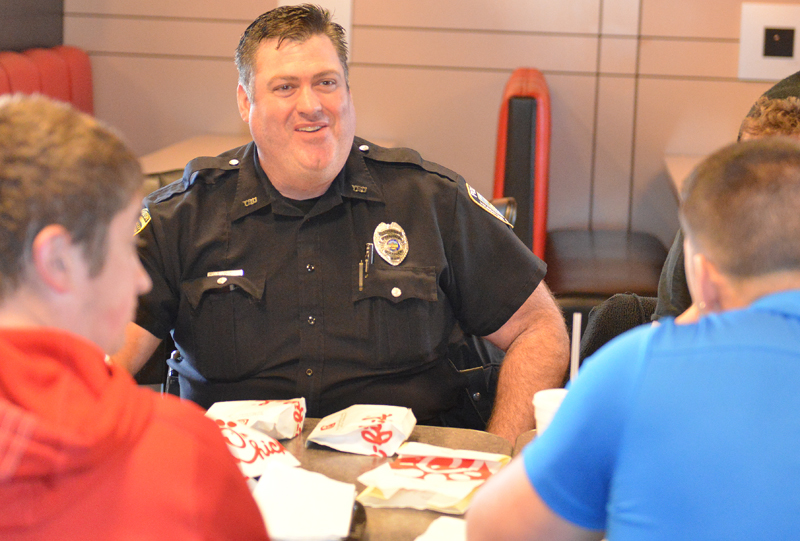 YSU Police Officer Donald Cox eats with students at Chik-Fil-A last month in Kilcawley Center as part of the YSUPD's new Lunch with a Cop initiative.