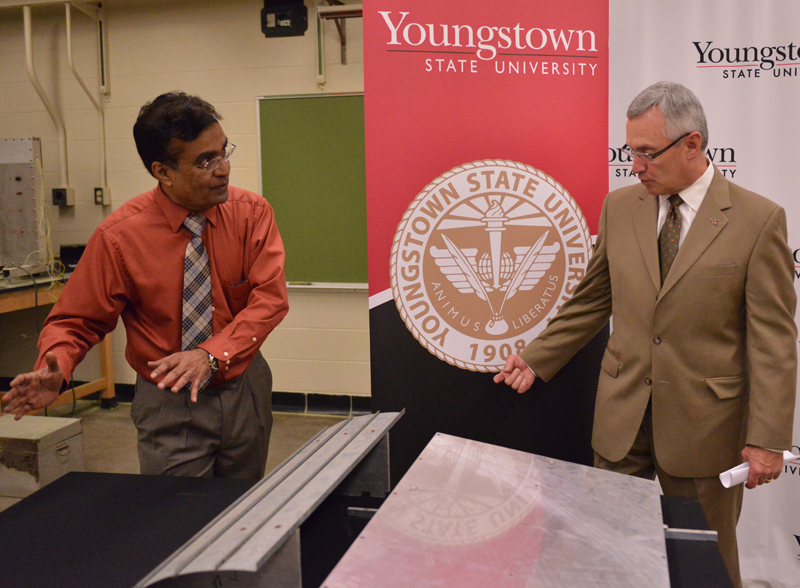 Ganest Kudav, YSU professor of Mechanical Engineering, explains the solar panel wind deflector to YSU President Jim Tressel. The university announced today that Kudav's design has been awarded a federal patent.