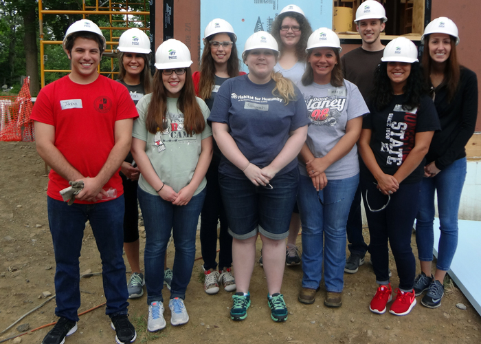 YSU students participating in the 2015 Nonprofit Leadership Summer Honors Internship Program are, left to right, front row, Jordan Wolfe, Leah Ferraro, Savannah Taylor, Marcy Angelo, Joey DeLisio; back row, Karli Rupert, Lindsey Farran, Jena Bushong, Eric Haughey, Kendal Malsch. They are pictured at the Habitat for Humanity work site in Salem, Ohio.