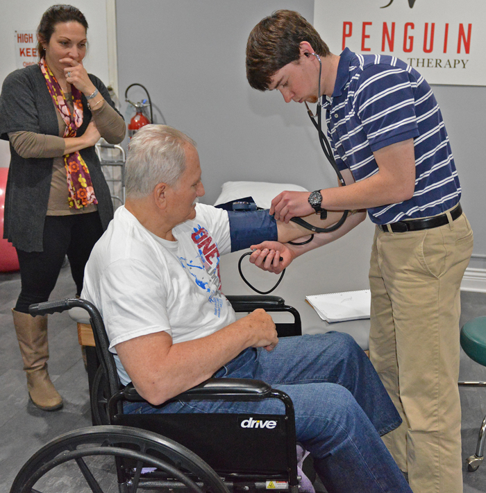 Cara Carramusa, instructor of Physical Therapy, looks on as student Ben Vetch takes the blood pressure of a patient at the Midlothian Free Health Clinic in First Presbyterian Church on Wick Avenue.