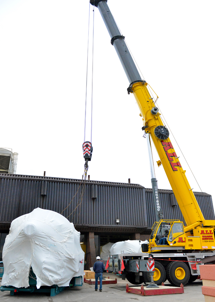 Workers prepare to move a boiler into the utility building at YSU as part of the installation of the university's new steam plant.
