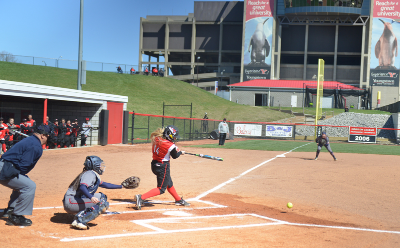 With Stambaugh Stadium towering in the distance, Penguin outfielder Sarah Dowd connects during a recent softball contest at the YSU field west of Fifth Avenue. Catch a Penguins game on campus this spring!