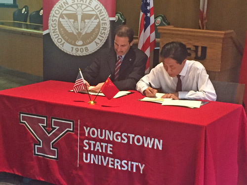 YSU Provost Martin Abraham, left, and Professor Li Jinsong of Chengdu sign the agreement in Tod Hall at YSU.