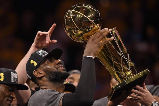 Lebron James celebrates with the Larry O'Brien Trophy.